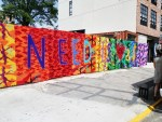 "Olek's response to the prompt ""Transform Today"" was this crocheted mural, which read ""All we need is love and money."""
