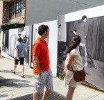 Williamsburg passersby look at Danish photographer Asger Carlsen's surreal vinyl photographs that he pasted on a construction fence.