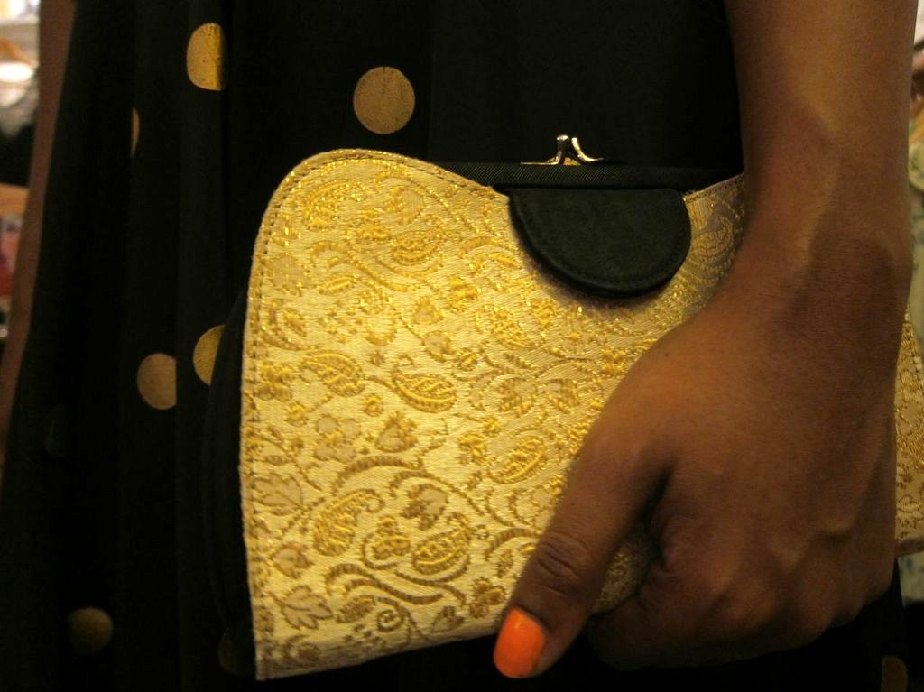 "Annette completes her outfit with a 1950s clutch that Amanda found at an estate auction. It's reversible, with gold brocade on one side and black velvet on the other, with a gold clasp. Annette keeps the brocade side out. ""The velvet is a nice little secret,"" she says."