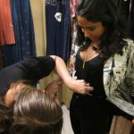 Dusty Buttons owner Amanda Loureiro measures Annette's waistline before she goes into the dressing room.