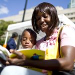 "Carletha Woodley-Alves reads ""Curious George"" with her daughter Soretta. (Photo: Meghan White)"