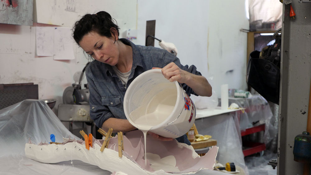 Murray's assistant Ruth Irving pours gypsum mixed with water into a mold of a model's leg. (Photo: Karissa Gall)