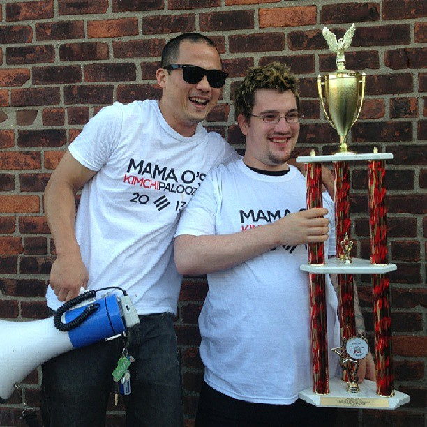 A previous kimchi eating contest winner, with trophy (image via Mama O's)