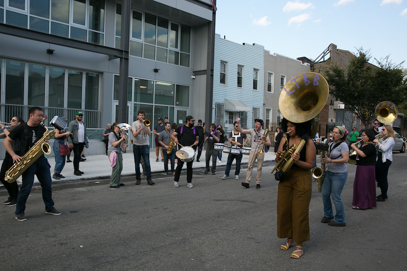 L train brass band parading in front of Pine Box Rock Shop.