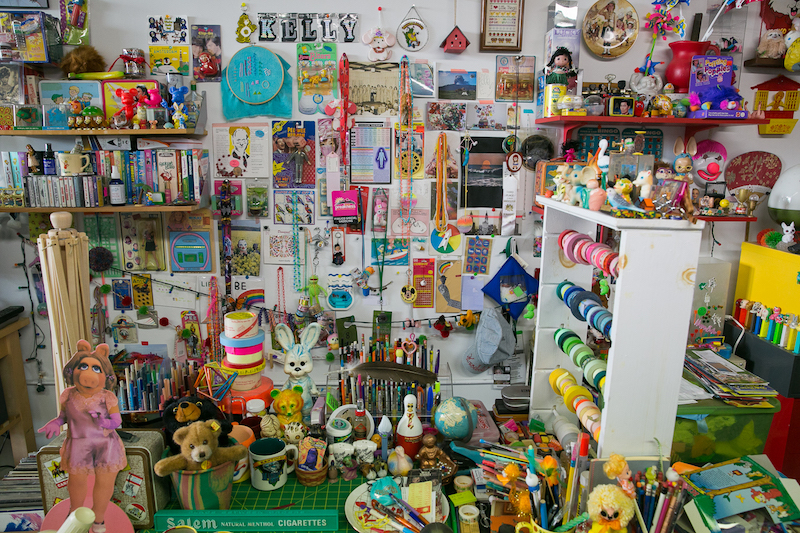 Kelly McCafferty's large pieces seemed like something out of the thick scrapbooks on a nearby table, except they were made with yarn pieces, beads, tiny toys, pins, etc.  Her desk area, shown here, was more of a 3D version of her wall hangings.